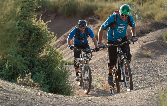 mountain biker leaning forward to get up steep hill